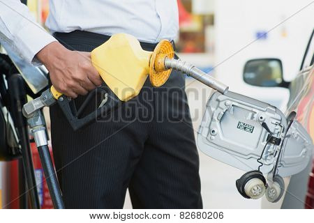 Close up Asian man pumping gasoline fuel in car at gas station.