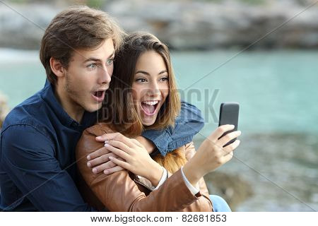 Shocked couple watching a smart phone on holidays on the beach poster