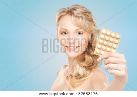 people, beauty, healthcare and medicine concept - happy young woman holding package of pills over blue background