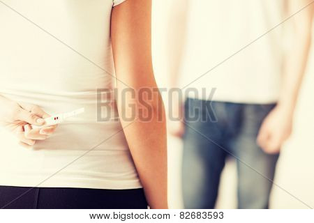 close up of woman hands hiding pregnancy test from man