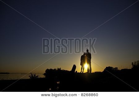 Silouette Of Two People Standing On A Bank