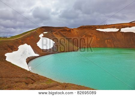 Picturesque Krafla lake in the crater of an extinct volcano. Lake water bright green color. On the shores lie snowfields from last year