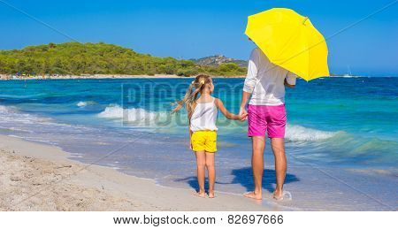 Little girl and young dad at white beach with yellow umbrella