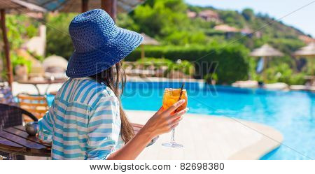 Young woman with cocktail in tropical cafe at exotic resort