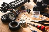 Building model cars. Radio control car assembly scene, RC car assembly on wooden work desk and tools. Natural lighting. poster
