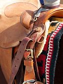 Fancy leather saddle strapped on over a brand new blanket poster
