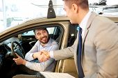 auto business, car sale, consumerism, gesture and people concept - happy man with car dealer making deal and shaking hands in auto show or salon poster