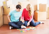 Young couple moving in a new home. Wife and husband selecting a new color for a condo. poster