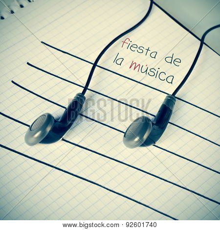 a pair of earphones placed on a staff drawn on a notepad simulating musical notes, and the text fiesta de la musica, world music day written in spanish