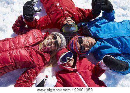 Overhead Shot Of Family Having Fun On Winter Holiday