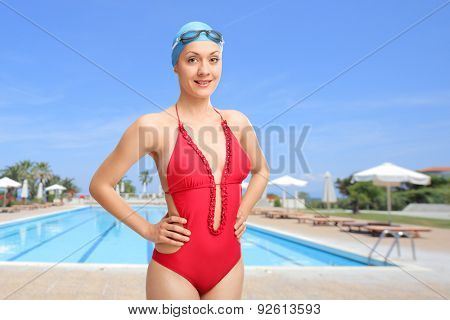 Young woman in red swimsuit wearing a blue swimming cap and goggles and posing in front of an open swimming pool