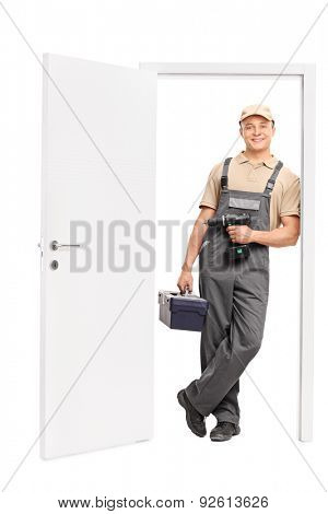 Full length portrait of a young male worker holding a toolbox and a hand drill and leaning against the frame of an open door isolated on white background