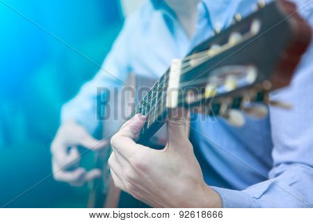 Young musician playing at acoustic guitar. Blue lensflare