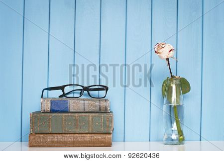 Books Pile, Glasses And White Rose In The Bottle