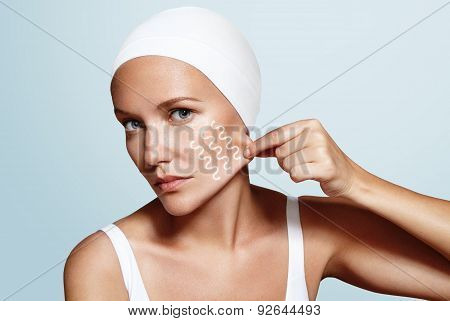 woman pinched skin on her face with a fingers lines on her face poster