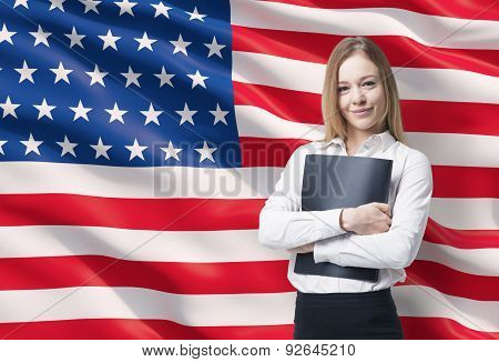 Smiling Business Lady In A White Shirt With A Black Folder. United States Flag As A Background.