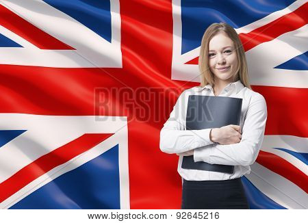 Smiling Business Lady In A White Shirt With A Black Folder. Great Britain Flag As A Background.