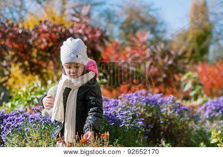 Little girl walks through the autumn colorful garden