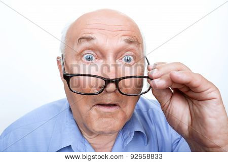 Surprised grandfather holding glasses