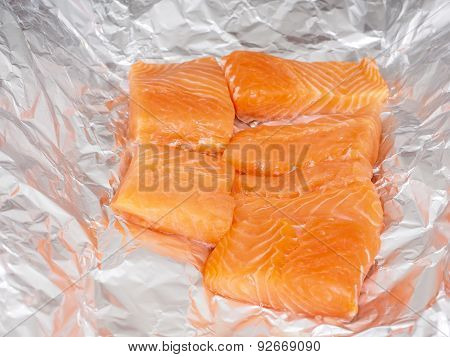 Closeup Of Unseasoned Salmon Pieces In Aluminum Foil