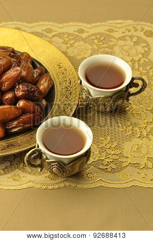 Two ornamental cups filled with arabic black tea with a golden plate full of dates.