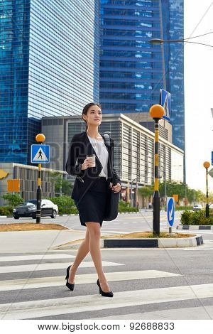 asian chinese business woman crossing street walking to work with coffee drink and bag in urban city district