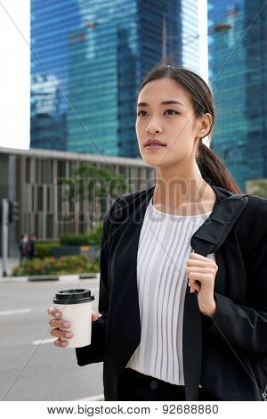 asian chinese business woman walking to work with coffee drink and bag in urban city district