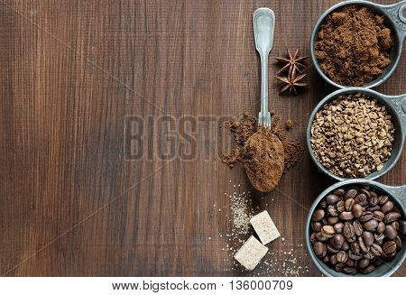 Coffee beans instant coffee and ground coffee in a metal measuring cup as well as sugar cubes a teaspoon and star anise on dark wooden background with space for text; top view flat lay overhead view