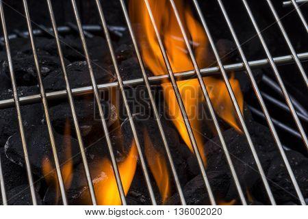 A new flaming hot charcoal grill closeup.