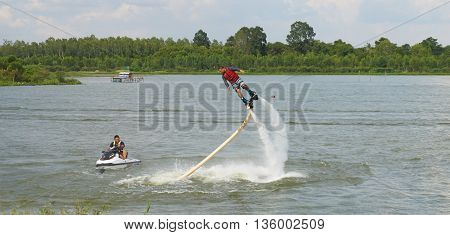 MUSEUM SERPENT KARK, YASOTHON, THAILAND - JUNE 19, 2016: Man ride on flyboard; an extreme water sport at public park.