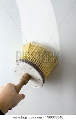 Wall being painted white with brush