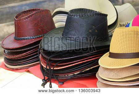 stacks of broad-brimmed leather and straw hats for sale at Cape Samila Beach, Songkhla, Thailand