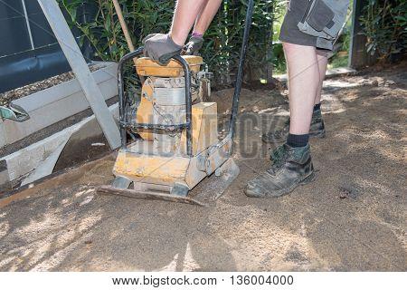 gardener is flattening the ground in the garden