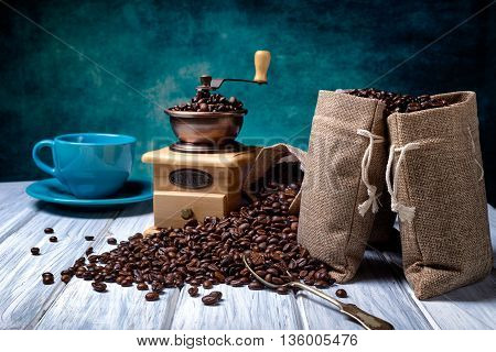 Coffee seeds in spoon with some jute bags filled with coffee and coffee grinder