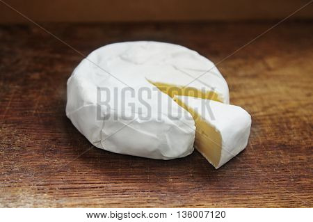 Creamy Brie with cut off piece on rustic wooden background.