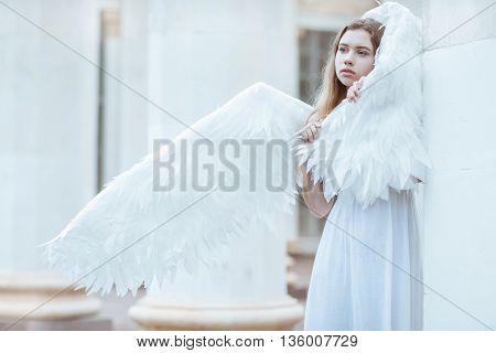 Girl with white wings wrapped in a wing and looks aside