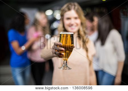 Smiling girl showing a beer with her friends in a nightclub