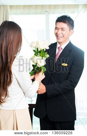 Asian Chinese Hotel Manager or director or supervisor welcome arriving VIP guest with roses on arrival in luxury or grand hotel