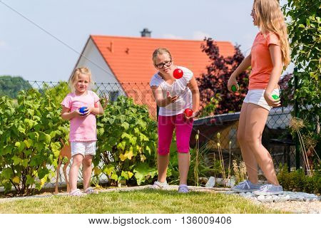 Three sisters playing bocce in garden front or their home in summer