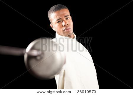 Portrait of swordsman practicing with fencing sword on black background