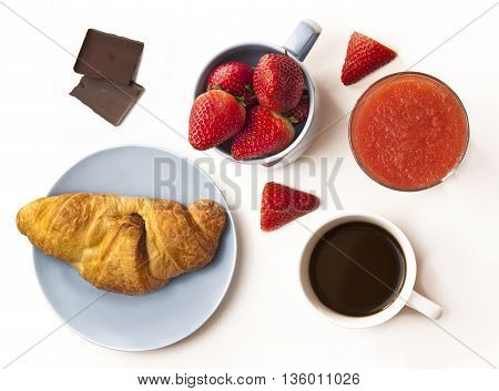 A photo of a healthy breakfast: a cup of coffee a mug with fresh strawberries a strawberry smoothie and a fresh croissant with pieces of dark chocolate shot from above on a white background