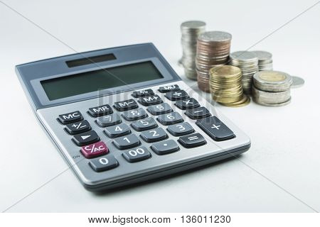 Calculator and Thai coin stack on white background
