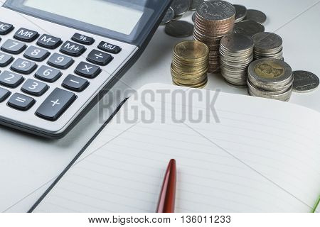 Calculator red pen Thai coin stack and notebook