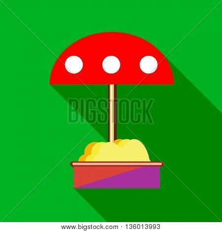 Childrens sandbox with red umbrella icon in flat style on a green background