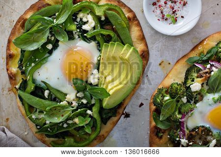 Breakfast pizza on pita with baked egg, spinach and green vegetables