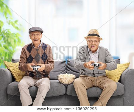 Two joyful seniors playing video games seated on a gray sofa at home poster