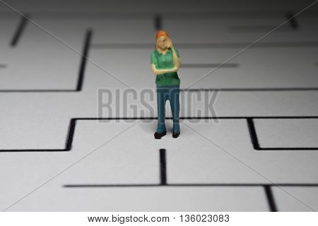 Little Person Standing in a Maze Thinking