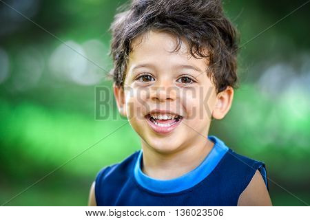Happy mulatto boy child is smiling enjoying adopted life. Portrait of young boy in nature park or outdoors. Concept of happy family or successful adoption or parenting.
