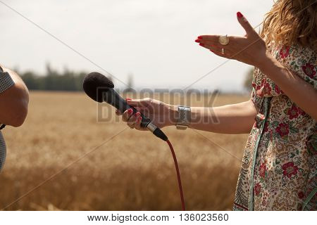 Female journalist making media interview with a farmer