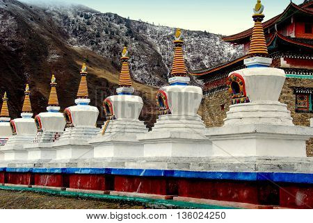 Ganzi, China - April 19 2012: A row of white dagobas with yellow ringed spires at the Xiabosang Tibetan monastery